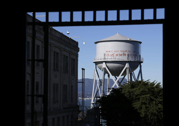 "FILE - This Jan. 14, 2013, file photo, shows a restored water tower with words that read ""Peace and Freedom Welcome Home of the Free Indian Land"" seen through an entryway to the main cell house on Alcatraz Island in San Francisco. The words were first written on the water tower during the Native American occupation. The week of Nov. 18, 2019, marks 50 years since the beginning of a months-long Native American occupation at Alcatraz Island in the San Francisco Bay. (AP Photo/Eric Risberg, File)"