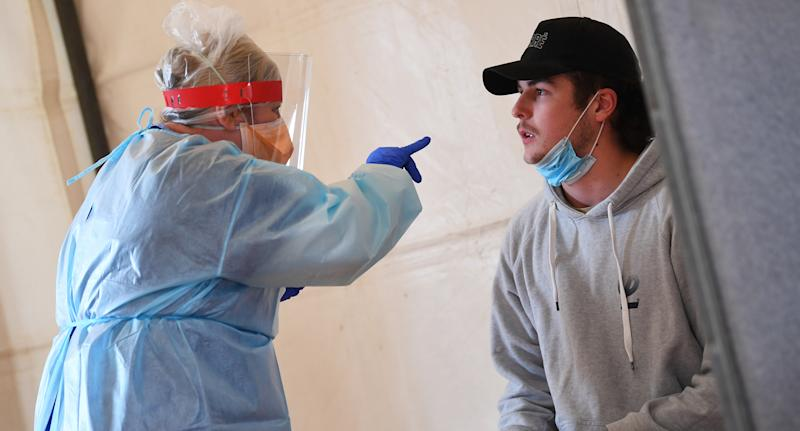 A healthcare worker conducts a test on a patient at a pop-up Covid19 testing centre at the Kilmore Memorial Hall in Kilmore, Victoria. Source: AAP