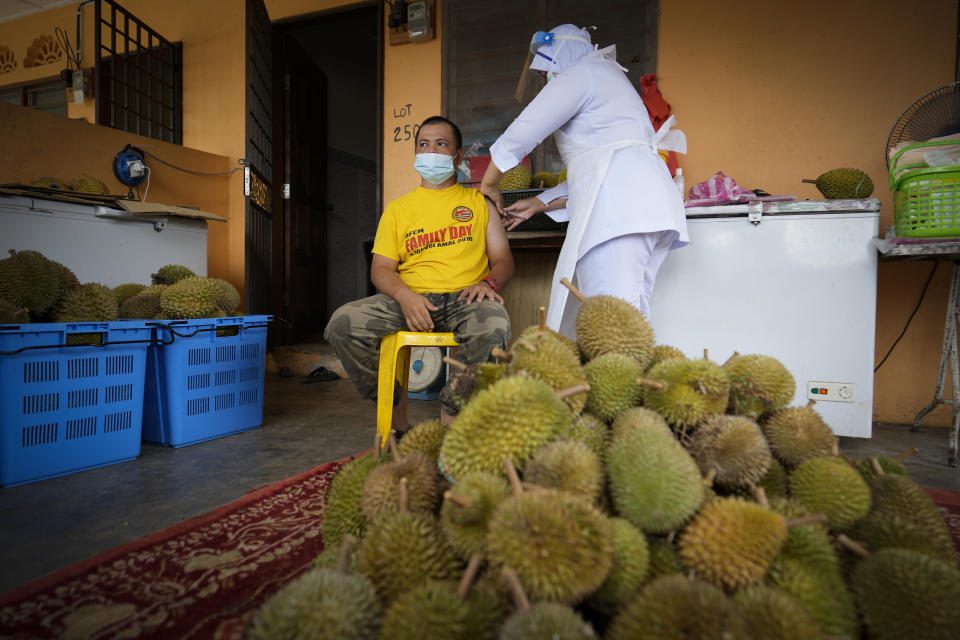 A nurse administers a Pfizer COVID-19 vaccine to an durian fruit vendor at his house in rural Sabab Bernam, central Selangor state, Malaysia, Tuesday, July 13, 2021. Medical teams are going house to house in rural villages to reach out to elderly citizens as the government seeks to ramp up its vaccination program. Despite a strict lockdown, the pandemic has worsened with more than 844,000 confirmed cases nationwide and over 6,200 deaths. (AP Photo/Vincent Thian)