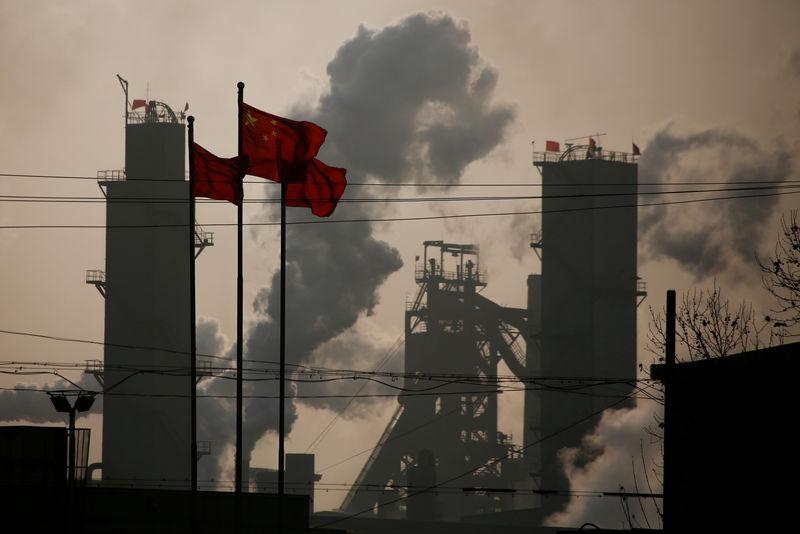 FILE PHOTO: Chinese national flags are flying near a steel factory in Wu'an