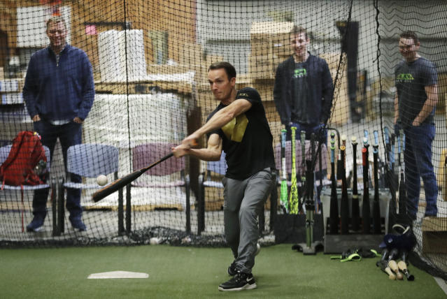 In this Feb. 8, 2018, photo, Brent Weidenbach, director of product management for Axe Bat, hits baseballs in the batting cage at the company's warehouse in Renton, Wash. Axe Bat is trying to revolutionize baseball with a simple concept -- a baseball bat handle that is shaped like the handle of an axe. (AP Photo/Ted S. Warren)