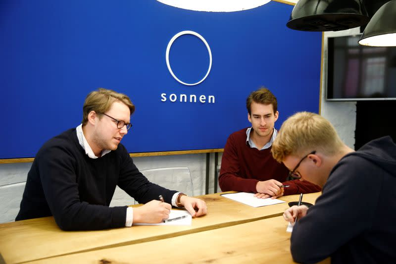 "FILE PHOTO: Employees of the startup ""sonnen"", formerly known as Sonnenbatterie, sit in a meeting room in Berlin"