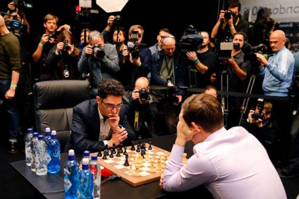 PHOTO: Cameras are trained on reigning world chess champion, Norway's Magnus Carlsen and challenger, Fabiano Caruana from the U.S., as they play the first game of the tie-break matches of the 2018 World Chess Championship in London on Nov. 28, 2018. (Tolga Akmen/AFP/Getty Images)