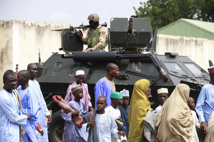 """Nigeria soldiers provide security on top of an armored personal carrier during Eid al-Fitr prayers at Ramat square in Maiduguri, northeastern Nigeria, Thursday, Aug. 8, 2013. Nigerians in the birthplace of an Islamic uprising gripping the northeast celebrated the Muslim holy day of Eid al-Fitr on Thursday with devout prayers and a joyful show of adulation for their king that attracted more than 10,000 people. It was the first durbar in three years in the city of Maiduguri and the joy that it could take place - albeit amid massive security - was heard in the cries of ululating women, screams of delight from children and men chanting """"Long live the king!"""" (AP Photo/Sunday Alamba)"""
