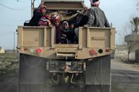 Iraqi families fleeing Mosul's Al-Tayaran neighbourhood sit in the back of a military truck on February 28, 2017, during an offensive by Iraqi forces to retake the area from Islamic State (IS) group fighters