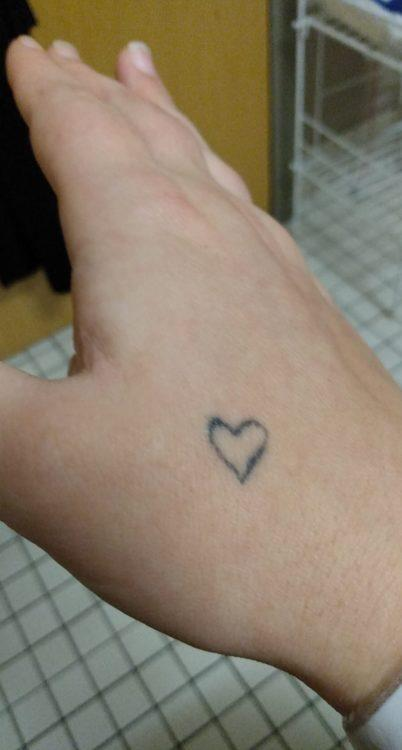 Mae shows the viewer a tattoo of a heart, which is located on her hand.