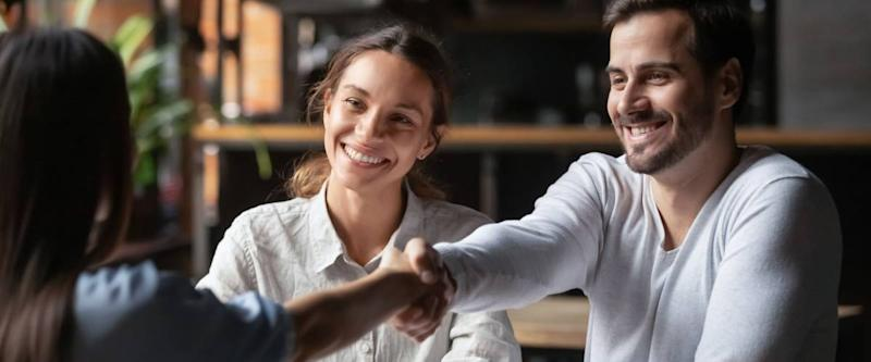Happy smiling millennial couple get acquainted with female real estate agent meeting together in cafe.