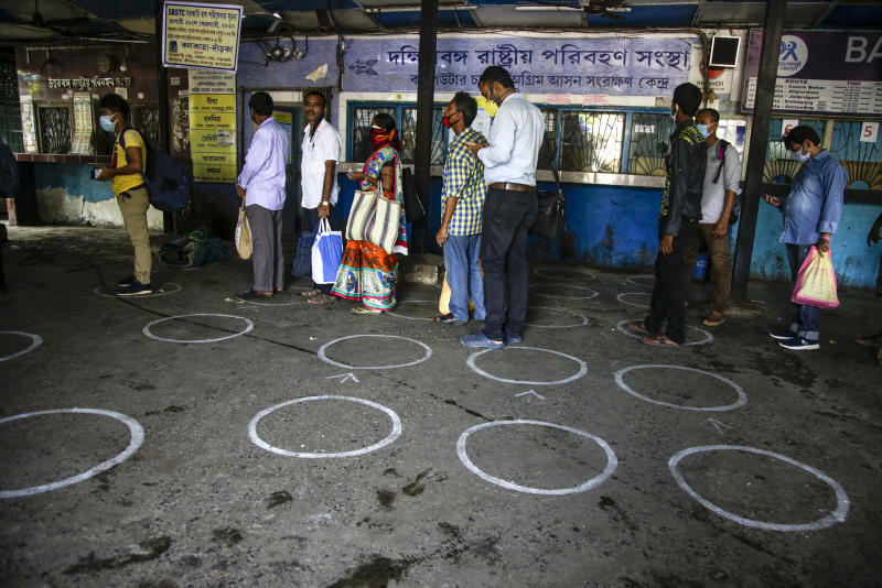 People stand in a queue to book bus tickets to travel to places outside the state in Kolkata, in the eastern Indian state of West Bengal, Wednesday, June 3, 2020. More states opened up and crowds of commuters trickled onto the roads in many of India's cities on Monday as a three-phase plan to lift the nationwide coronavirus lockdown began despite an upward trend in new infections. (AP Photo/Bikas Das)