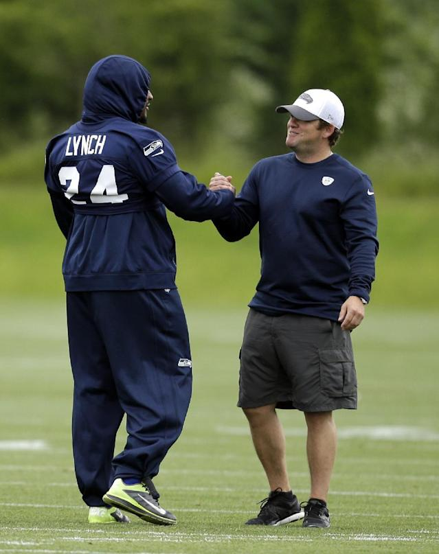 Seattle Seahawks general manager John Schneider, right, greets Marshawn Lynch at a football minicamp practice Tuesday, June 17, 2014, in Renton, Wash. (AP Photo/Elaine Thompson)