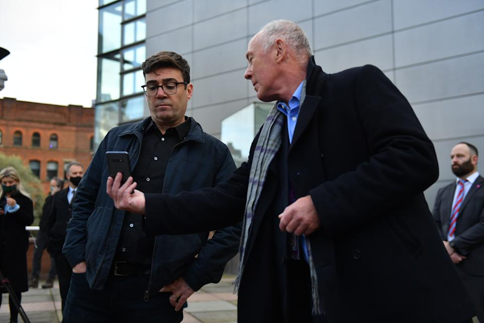 <strong>Greater Manchester mayor Andy Burnham (left) with leader of Manchester City Council Sir Richard showing him when the measures will come into force after speaking to the media outside Bridgewater Hall, Manchester.</strong> (Photo: Jacob King - PA Images via Getty Images)