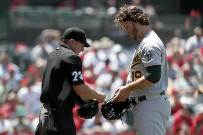 Home plate umpire Tripp Gibson, left, checks the equipment of Oakland Athletics starting pitcher Cole Irvin during the third inning of a baseball game against the Los Angeles Angels in Anaheim, Calif., Saturday, July 31, 2021. (AP Photo/Alex Gallardo)