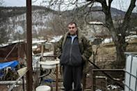 Khachik Stepanyan outside the houses he and his family are staying in, which is only a few meters away from the home they were forced to abandon