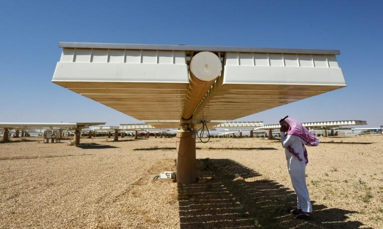 A man talks on his phone under a solar panel on March 29, 2018 in Uyayna, north of Riyadh, where Saudi Arabia is building what is set to be the world's biggest solar plant