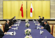 China' Foreign Minister Wang Yi, second left, meets with his Japanese counterpart Toshimitsu Motegi, right, amid the coronavirus outbreak, in Tokyo on Tuesday, Nov. 24, 2020. Wang met Motegi on Tuesday to discuss ways to revive their pandemic-hit economies as well as regional concerns over China's growing influence. (Issei Kato/Pool Photo via AP)