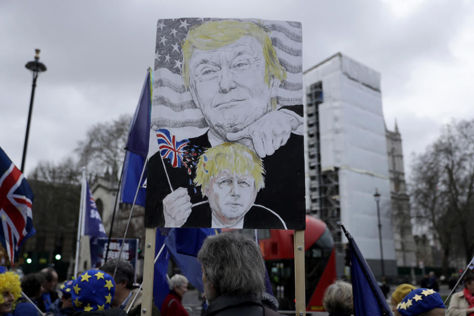 FILE - In this Jan. 8, 2020 file photo remain in the European Union, anti-Brexit protesters, including one with a placard depicting British Prime Minister Boris Johnson under the thumb of U.S. President Donald Trump, demonstrate outside the Houses of Parliament in London, on the day of Prime Minister's Questions taking place inside. (AP Photo/Matt Dunham, File)