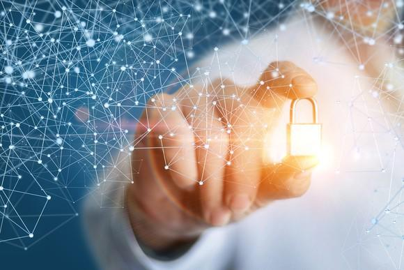 A person holding a glowing golden lock, surrounded by latticework that's representative of blockchain technology.