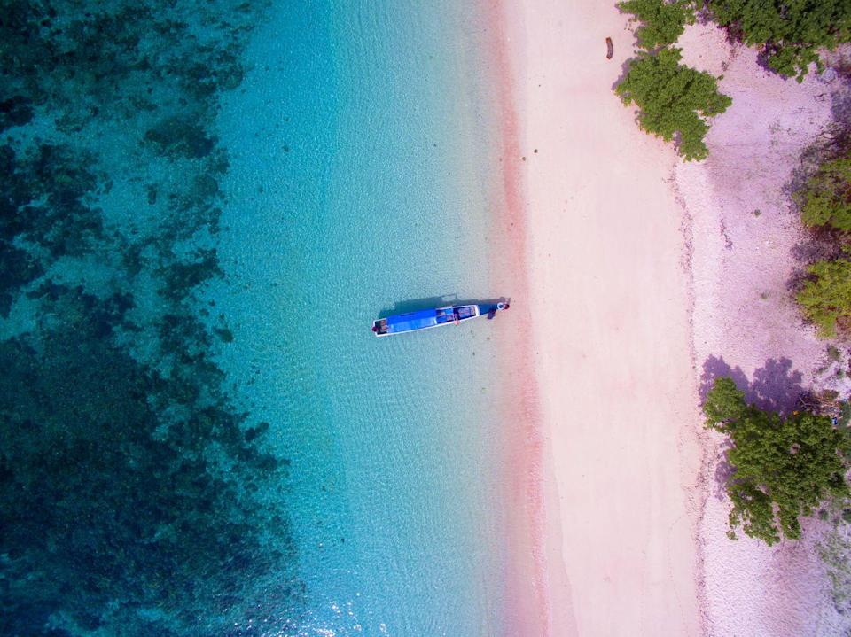 """<p>The pink coastline of Komodo Island gets its glowing hue from the degradation of the red coral reefs mixing with the white sand. Also known as Pantai Merah, the beach is a part of Indonesia's <a href=""""https://www.komodonationalpark.org/"""" rel=""""nofollow noopener"""" target=""""_blank"""" data-ylk=""""slk:Komodo National Park"""" class=""""link rapid-noclick-resp"""">Komodo National Park</a> which spans 29 volcanic islands with a variety of terrains and fauna. The island is technically uninhabited, but the park welcomes people to snorkel and discover vibrant coral reefs. However, be sure to be on the lookout for komodo dragons who call the island home. </p>"""