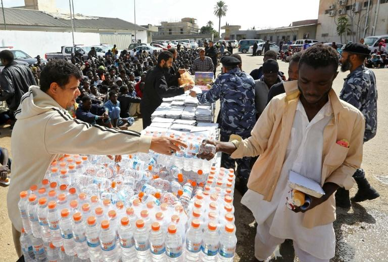 Illegal migrants receive food during a visit of the UN envoy to Libya at a detention centre in the Libyan capital tripoli on February 21, 2017