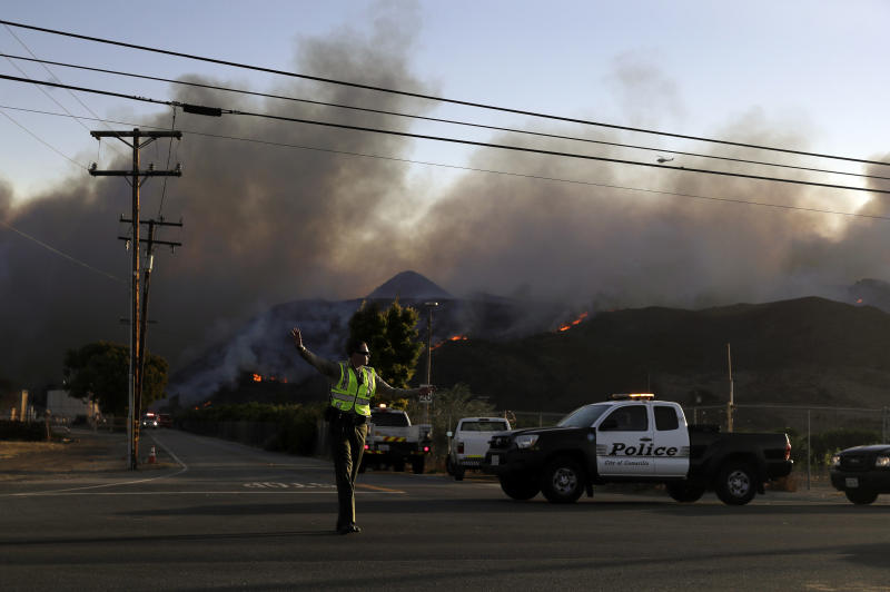 A police officer mans a checkpoint in front of an advancing wildfire Thursday, Nov. 8, 2018, near Newbury Park, Calif. The Ventura County Fire Department has also ordered evacuation of some communities in the path of the fire, which erupted a few miles from the site of Wednesday night's deadly mass shooting at a Thousand Oaks bar. (AP Photo/Marcio Jose Sanchez)