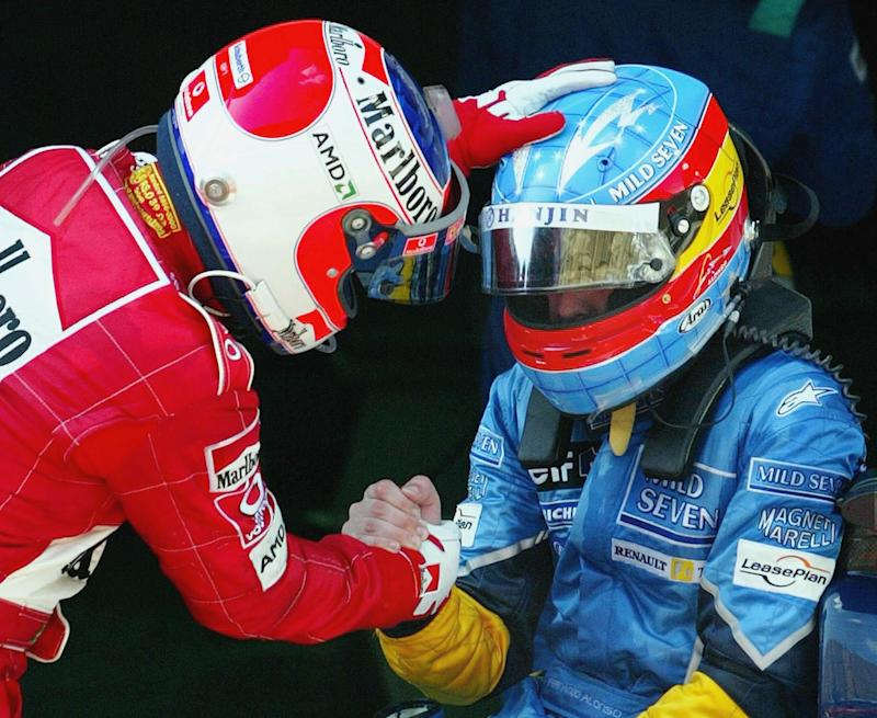 Ferrari's Rubens Barrichello of Brazil (L) shakes hands with Renault's Fernando Alonso of Spain after they finished second and third respectively in the Malaysian Grand Prix in Sepang, 23 March 2003. McLaren's Kimi Raikkonen of Finland won the race in a time of 1hr 32min 22.195sec. AFP PHOTO/Jimin LAI (Photo by JIMIN LAI / AFP) (Photo credit should read JIMIN LAI/AFP via Getty Images)