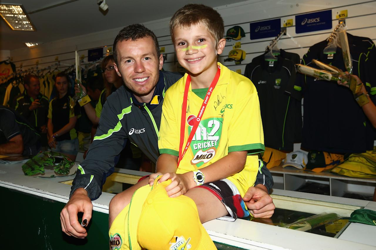 BRISBANE, AUSTRALIA - NOVEMBER 10:  Peter Siddle of Australia poses with a fan at a merchandise stand as rain delays the start of play on day two of the First Test match between Australia and South Africa at The Gabba on November 10, 2012 in Brisbane, Australia.  (Photo by Mark Kolbe/Getty Images)