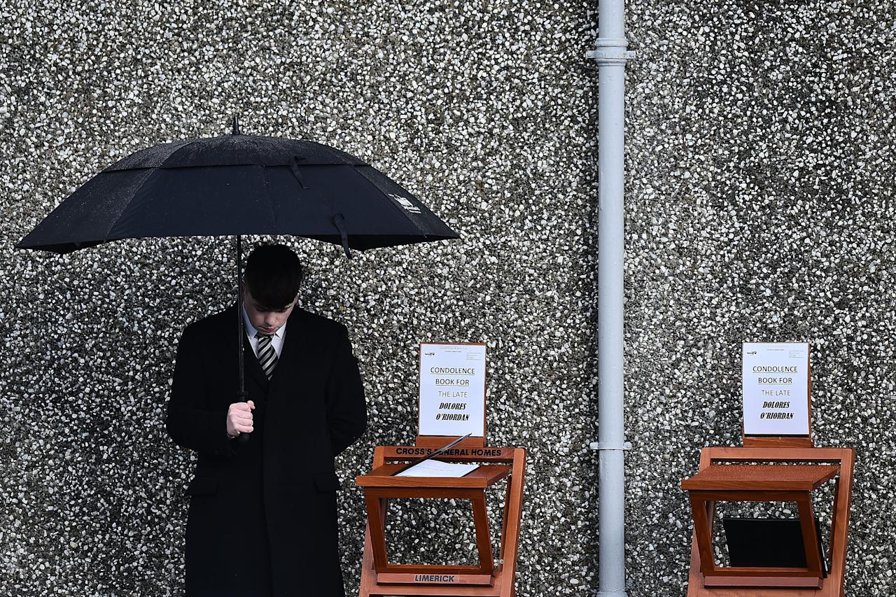 <p>An undertaker stands beside a book of condolence outside St Ailbe's parish church in Ballybricken at Dolores O'Riordan's funeral on Jan. 23, 2018 in Limerick, Ireland. Photo from Charles McQuillan/Getty Images. </p>