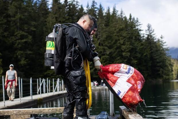 Henry Wang with Divers for Cleaner Lakes and Oceans pulls up a bag of garbage he helped collect from the bottom of Sasamat Lake in Belcarra Regional Park. (Gian Paolo Mendoza/CBC - image credit)