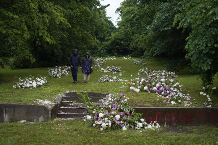 People hold hands after leaving flowers besides others at a makeshift memorial beside stairs leading to a now empty lot near the historic greenwood district during centennial commemorations of the Tulsa Race Massacre, Monday, May 31, 2021, in Tulsa, Okla. (AP Photo/John Locher)