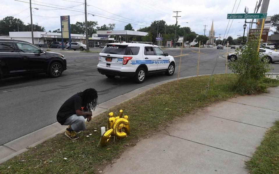 Timothy Moore kneels beside a memorial at the corner of Beatties Ford Road and Catherine Simmons Avenue on Tuesday, June 23, 2020, in memory of his cousins Christopher Antonio Gleaton, and Kelly Miller, two of the three people killed at an outdoor party the previous morning.