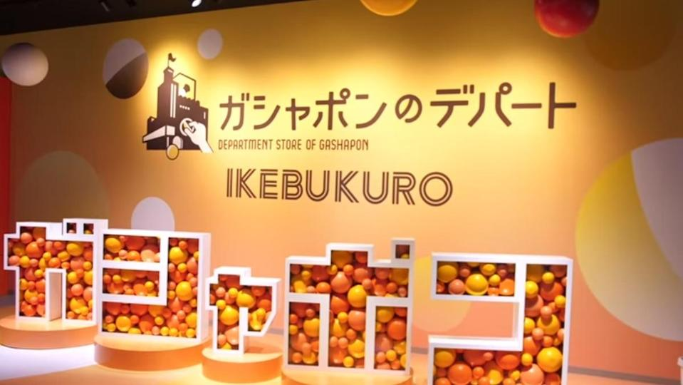a photo of orange and yellow plastic balls inside white geometric shapes with the word Ikebukuro and Gashapon department store written in japanese.