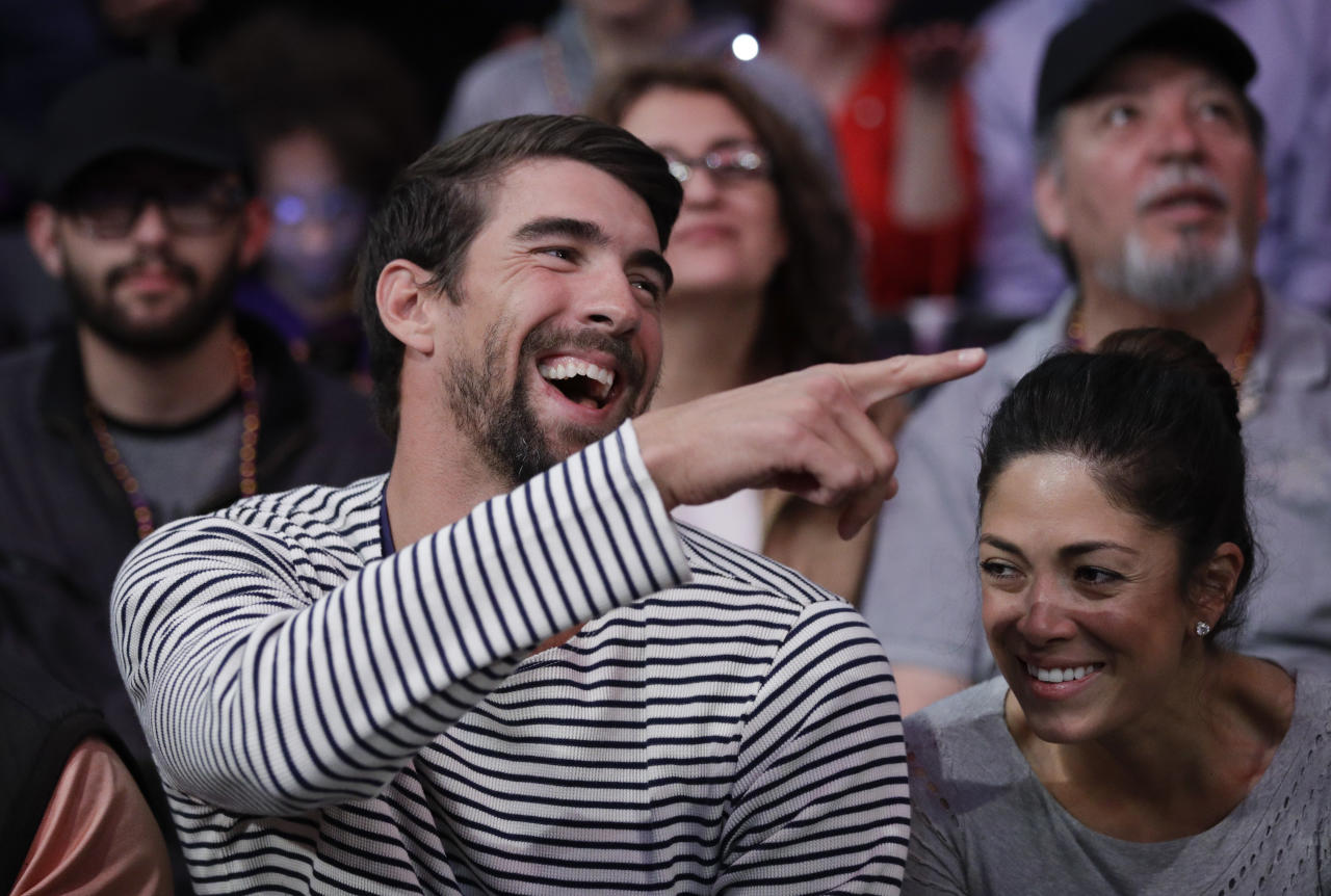 <p> FILE - In this March 21, 2017, file photo, Michael Phelps and his wife, Nicole Johnson, smile during an NBA basketball game between the Los Angeles Lakers and the Los Angeles Clippers in Los Angeles. If Phelps returns to competitive swimming, the demands of training would surely cut heavily into his family time. That's why, if he tries to predict what the future might hold, it doesn't include a sixth Olympics at Tokyo in 2020. (AP Photo/Jae C. Hong, File) </p>