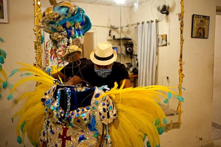 Leandro dos Santos adjusts a costume from last year's Carnival in Rio's Vila Isabel district.