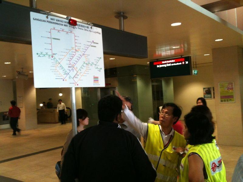 SMRT staff members giving assistance to stranded commuters at the station. (Yahoo! photo)