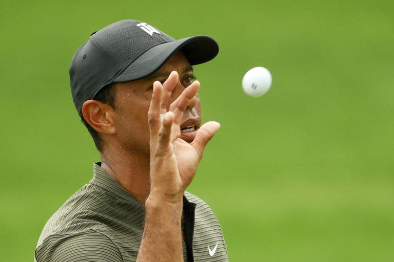 Defending champion Tiger Woods catches a ball on the 16th hole in the first round of the Masters at Augusta National