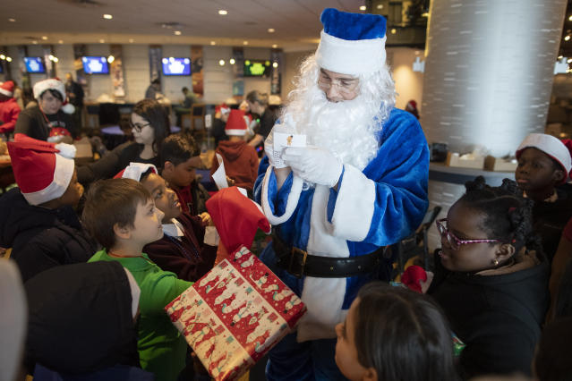 New York Mets outfielder Brandon Nimmo, dressed as Santa, signs autographs for local children during the team's annual Kids Holiday Party, Wednesday, Dec. 4, 2019, in New York. (AP Photo/Mary Altaffer)