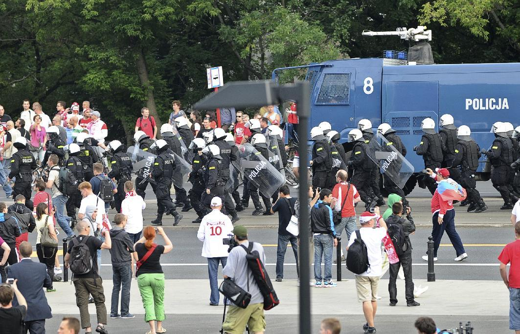 Police bring a water cannon as fans clash prior to the Euro 2012 soccer championship Group A match between Poland and Russia in Warsaw, Poland, Tuesday, June 12, 2012. Russian soccer fans clashed with police and Poland supporters in separate incidents in Warsaw on Tuesday, just hours before the two teams were to meet in an emotionally charged European Championship match. Several people were injured. (AP Photo/Alik Keplicz)