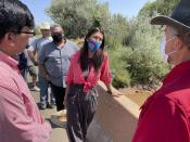 This Aug. 31, 2021 photo shows U.S. Rep. Teresa Leger Fernández, center, talking with acequia officials at a crossing over the Rio Chama during a tour near Abiquiu, New Mexico. The traditional irrigation systems known as acequias are facing pressure amid persistent drought and warming temperatures. (AP Photo/Susan Montoya Bryan)