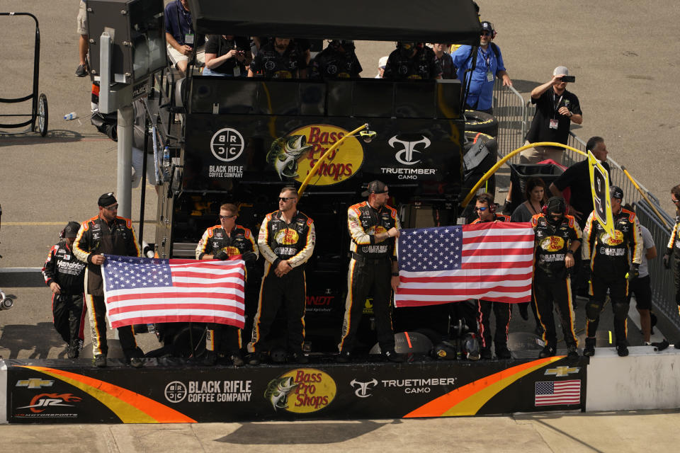 The pit crew of Noah Gragson (9) displays the U.S. flag during laps nine, ten and eleven during the NASCAR Xfinity auto race in Richmond, Va., Saturday, Sept. 11, 2021. (AP Photo/Steve Helber)