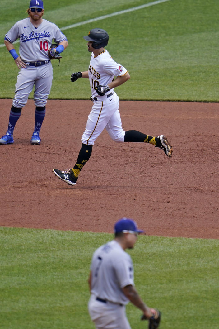 Pittsburgh Pirates' Bryan Reynolds, center, rounds the bases past Los Angeles Dodgers third baseman Justin Turner, left, after hitting a two-run home run off Dodgers starting pitcher Julio Urias, right, during the third inning of a baseball game in Pittsburgh, Thursday, June 10, 2021. (AP Photo/Gene J. Puskar)