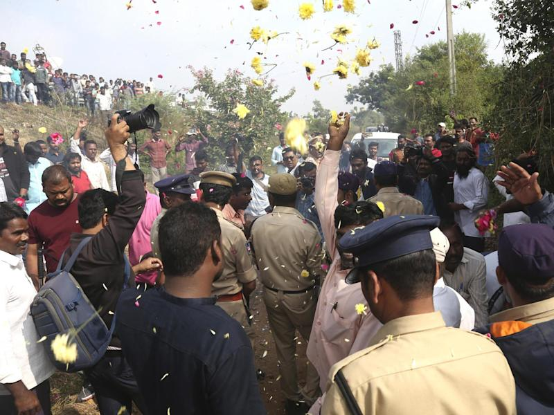 People throw flower petals on the Indian policemen guarding the area where rape accused were shot in Shadnagar on 6 December: Associated Press