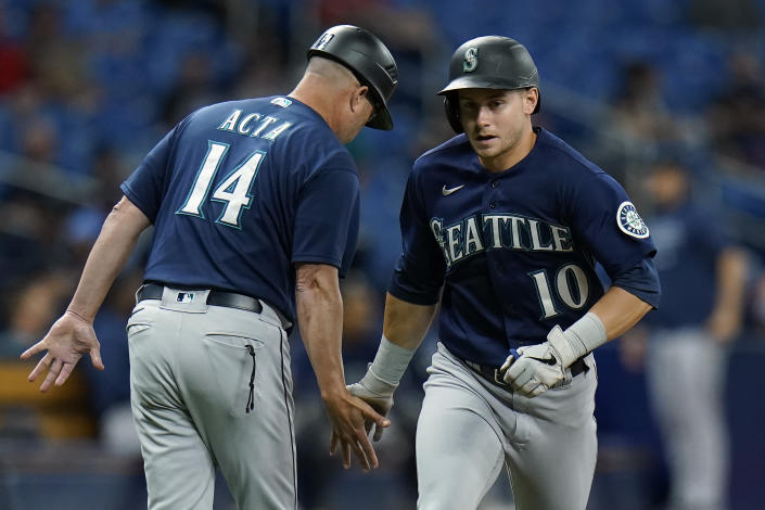Seattle Mariners' Jarred Kelenic (10) celebrates with third base coach Manny Acta (14) after his solo home run off Tampa Bay Rays pitcher Luis Patino during the fourth inning of a baseball game Tuesday, Aug. 3, 2021, in St. Petersburg, Fla. (AP Photo/Chris O'Meara)