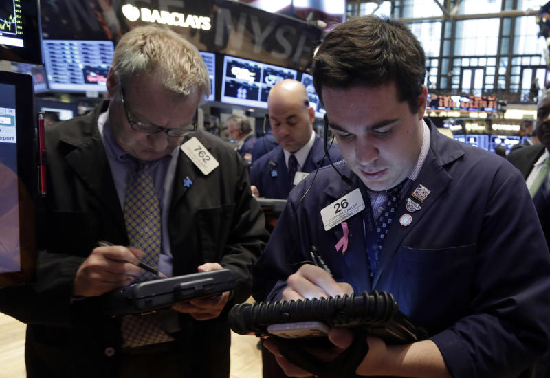 Joseph Lawler, right, works with fellow traders on the floor of the New York Stock Exchange Thursday, May 23, 2013. Stocks fell in early trading, extending a sell-off that began Wednesday afternoon, after Chinese manufacturing unexpectedly contracted and on concern that the Federal Reserve may ease back on its stimulus program. (AP Photo/Richard Drew)
