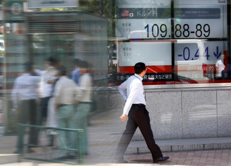 People walk past an electronic board showing exchange rate between Japanese Yen and U.S. Dollar outside a brokerage at a business district in Tokyo