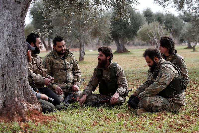 Ahmed Mansour and his comrades rest under an olive tree near Binnish