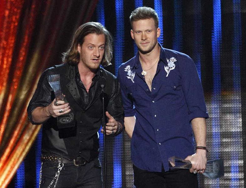 """Tyler Hubbard, left, and Brian Kelley of Florida Georgia Line accept their award at CMT """"Artists of the Year"""" show held at the Music City Center on Tuesday, Dec. 3, 2013, in Nashville, Tenn. (Photo by Wade Payne/Invision/AP)"""