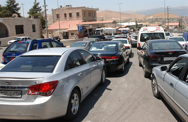 Syrians cross into Lebanon in private cars at the border crossing in Masnaa, Lebanon, about 40 kilometers (25 miles) from Damascus, Syria, Thursday, July 19, 2012. Private cars as well as taxis and buses carried thousands of people fleeing the violence in the Syrian capital. Syrian forces struck back against rebels Thursday with attack helicopters and shelling in Damascus, one day after an audacious rebel attack in the capital killed three leaders of the regime and left President Bashar Assad's hold on power increasingly tenuous. (AP Photo)