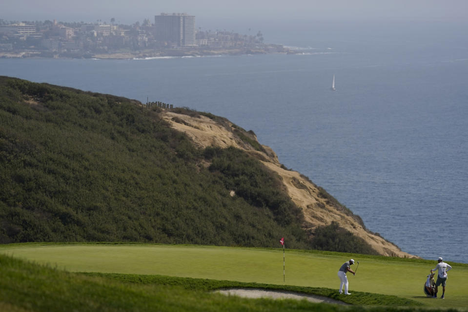 Dustin Johnson chips onto the third green during the first round of the U.S. Open Golf Championship, Thursday, June 17, 2021, at Torrey Pines Golf Course in San Diego. (AP Photo/Gregory Bull)