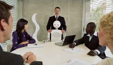 Robot and group of executives meeting in conference room