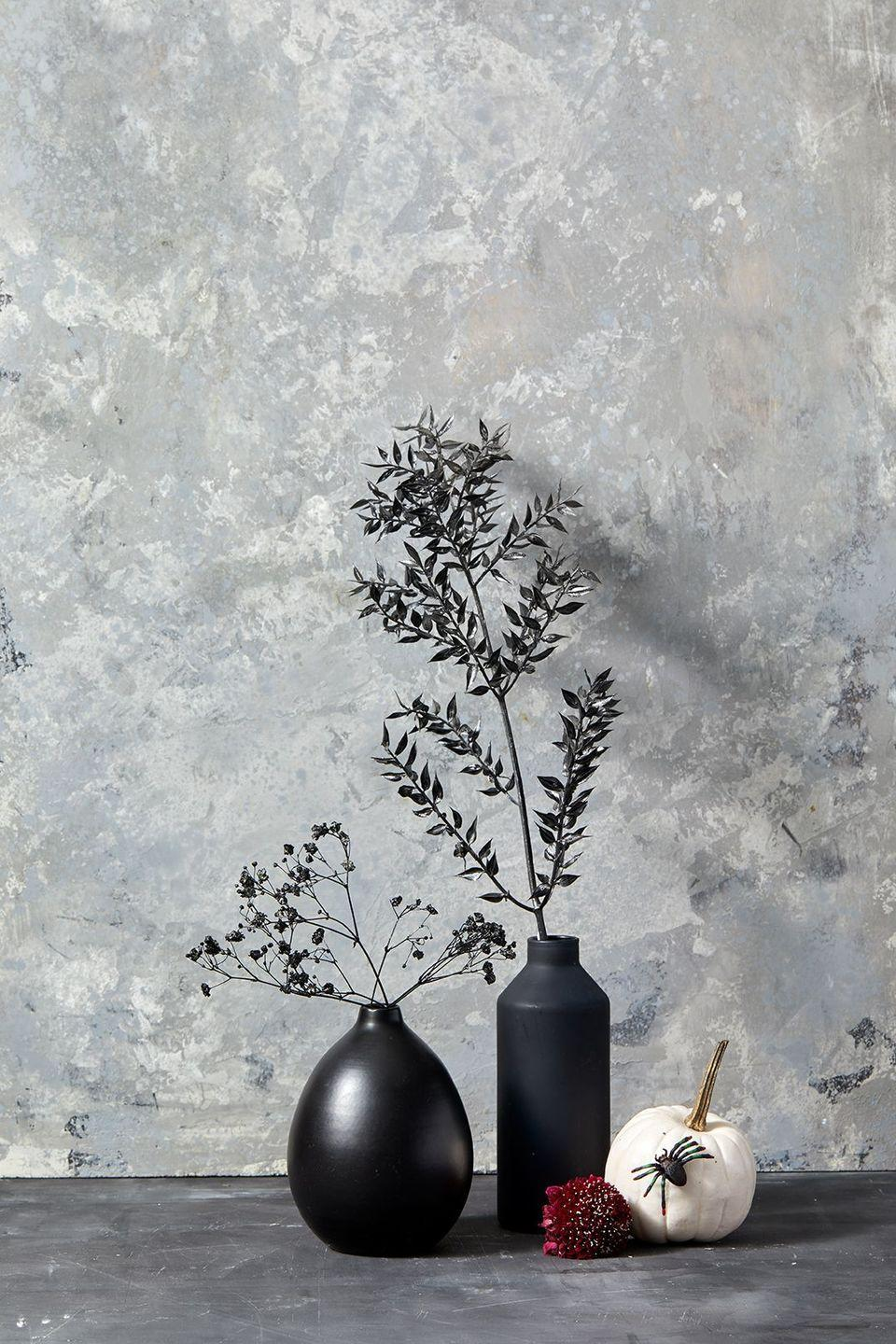 <p>Instantly add some drama to your space by spray painting branches of dried baby's breath black and using them as your centerpiece. </p>