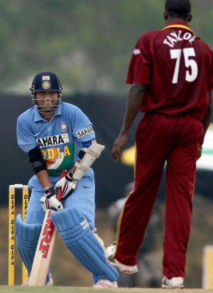 Kuala Lumpur, MALAYSIA:  Indian cricketer Sachin Tendulkar (L) shares a light moment with West Indian bowler Jerome Taylor after missing a ball during a one day international cricket match between India and the West Indies at The Kinrara Oval, Kuala Lumpur, 14 September 2006, as part of the continuing DLF Cup Tri-nation Series between India, Australia and West Indies.    Tendulkar scored 141 runs in 148 balls including thirteen boundaries and five sixes helping India to a score of 309 runs for the loss of five wickets in their alotted 50 overs after captain Rahul Dravid won the toss and elected to bat. The match was halted due to rain as the West Indies had scored 141-2 in reply to the Indian total.    AFP PHOTO/Saeed KHAN  (Photo credit should read SAEED KHAN/AFP/Getty Images)